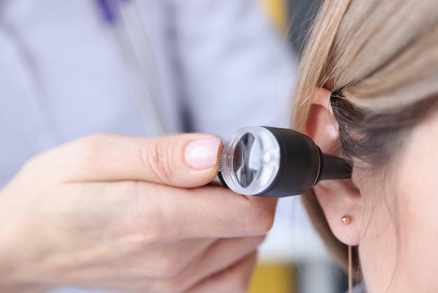 耳鼻咽喉科医が耳鏡のクローズアップを使用して患者の耳を見ています。