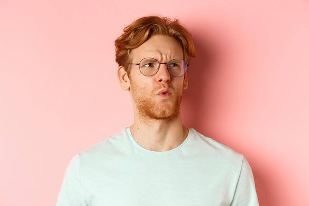 Ahi, è brutto. volto di un uomo dai capelli rossi che mostra pietà e si sente dispiaciuto per qualcuno, accigliato e guardando con compassione, in piedi su sfondo rosa