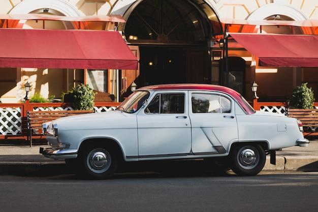 Oudoor выстрел ретро белый автомобиль стоит на асфальте на фоне кафе на улице