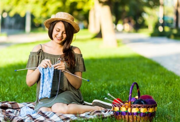 公園でoudoorsを編む若い女性