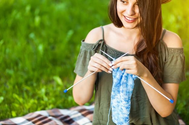 若い女性が公園でoudoorsを編み物
