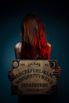 Ouija board for divination. girl holding a ouija board