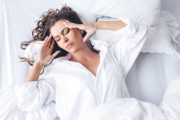Красивая кавказская женщина утром, лежа на белой кровати в белой рубашке, страдает головной болью / бессонницей / мигренью / стрессом