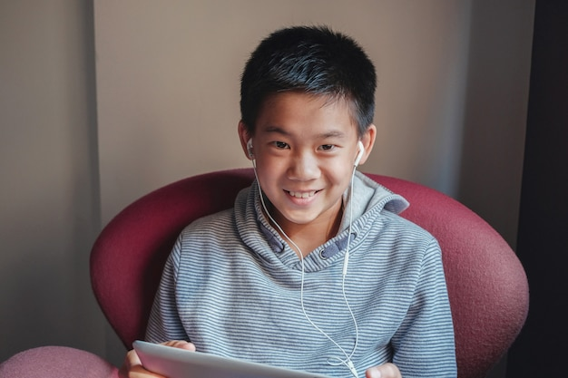 Oung  mixed asian preteen boy using digital tablet at home