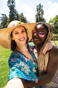 Молодая многорасовая женская пара делает селфи в парке вертикальное изображение лгбт-концепция отпуск