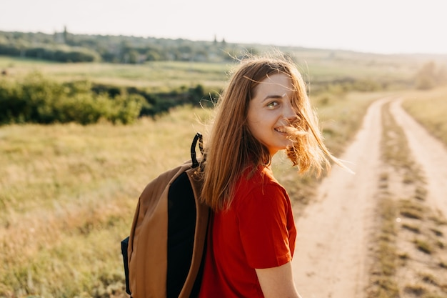 Молодая женщина с рыжими волосами и рюкзаком, идущая по тропинке, глядя в камеру, улыбается.