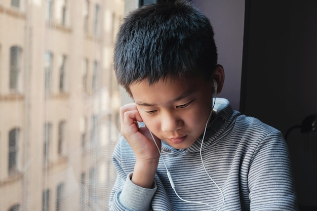Oung смешанный азиатский мальчик предподростковый, используя цифровой планшет на дому