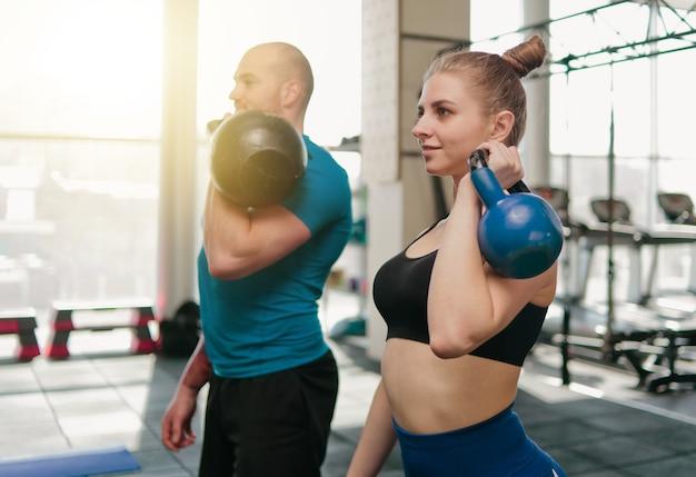 Ð¡複数のファンクショナルトレーニング。ジムでケトルベルで運動をしているスポーティな男性とフィットの女性