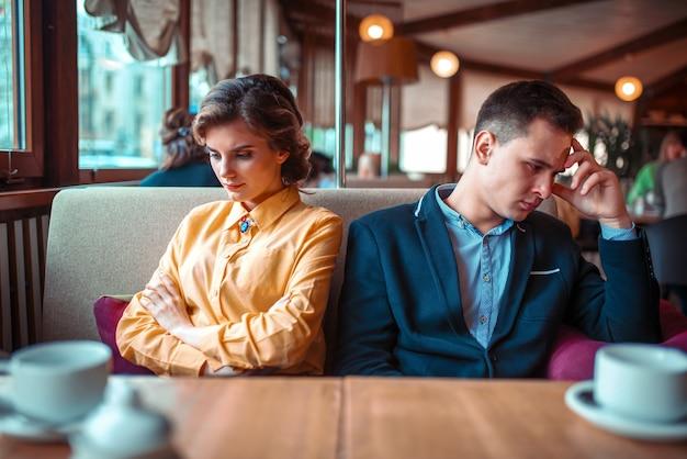 レストランに座っている機嫌の悪いカップル