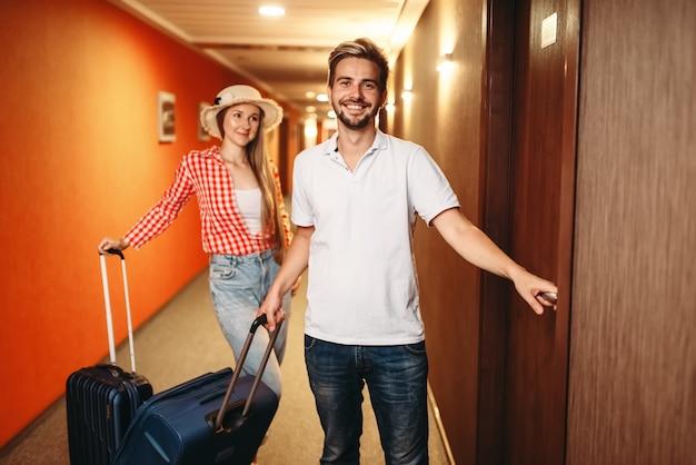 ホテルにチェックインするスーツケースを持ったカップル