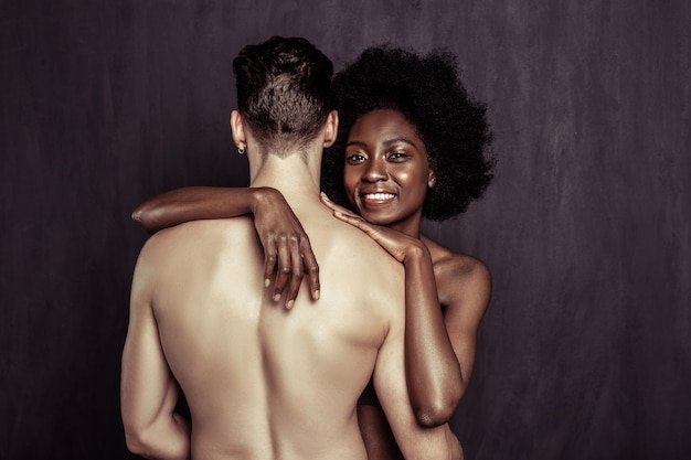 Our bodies. joyful naked woman smiling while hugging her beloved boyfriend