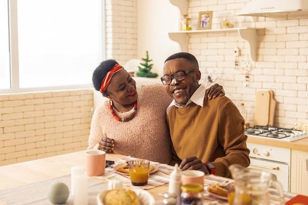 우리 아침. 아침 식사를하는 동안 부엌에 함께 앉아 긍정적 인 좋은 커플