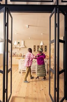 私たちのダンス。キッチンで踊りながらお互いに笑顔で幸せな喜びのカップル