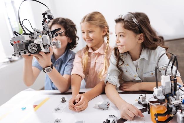 私たちの電子の友人。好奇心旺盛でスマートで楽しい子供たちがクラスに座って、技術プロジェクトに取り組んでいる間ロボットを使用しています