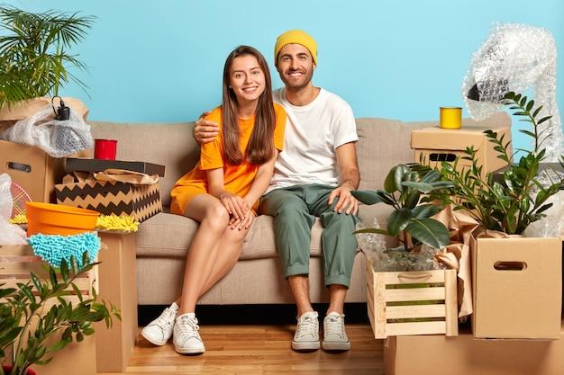 私たちの最初の家。新婚夫婦が新しいアパートに持ち物の入った箱を持ってくる