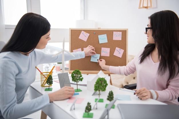 우리의 목표. 신진 움직이지 않는 여성과 학생이 함께 일하고 보드에 메모를 넣기