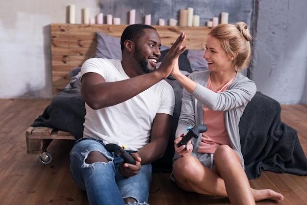 Наши счастливые времена. обрадованная международная молодая пара, наслаждающаяся видеоиграми, сидя в спальне и улыбаясь.
