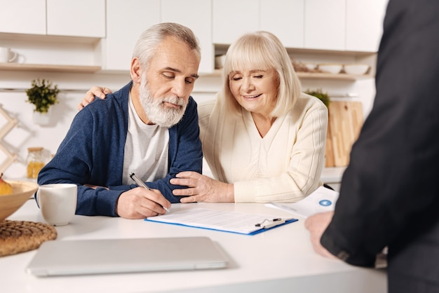 Our important day. smiling involved delighted elderly couple sitting at home and having meeting with broker while signing documents