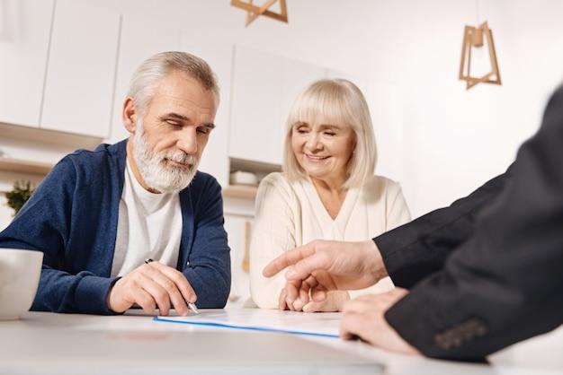 Наша важная покупка. решительная счастливая старшая пара сидит дома и встречается с финансовым консультантом при подписании соглашения