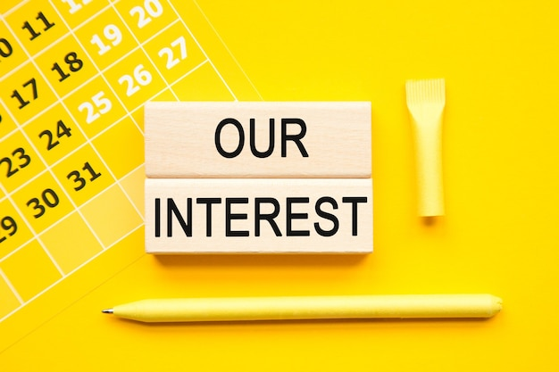큐브, 추상 달력, 노란색 바탕에 노란색 펜에 우리의 관심 비문. 비즈니스, 금융, 마케팅 개념을위한 밝은 솔루션 프리미엄 사진