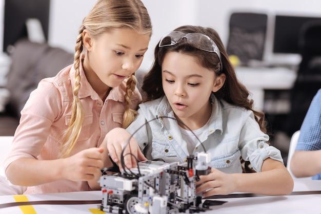 私たちの興味深いプロジェクト。学校に座ってロボットを組み立てながら授業を楽しんでいる驚いた驚いた賢い科学者たち