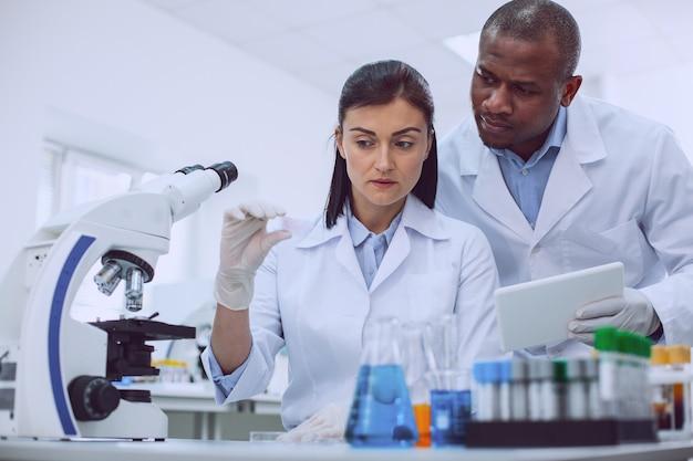 우리 실험실. 샘플을 들고있는 숙련 된 연구원과 태블릿을 들고 그 뒤에 서있는 그의 동료 프리미엄 사진