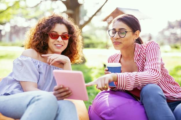 私たちの余暇。タブレットを持って彼女の友人と話している美しいインスピレーションを得た女性