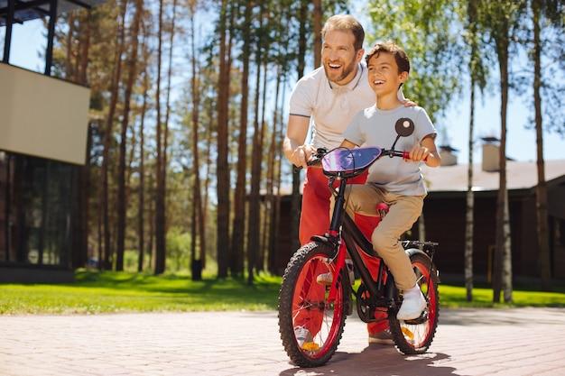 私たちの余暇。幸せな愛情のある父は笑顔で息子に自転車に乗るように教えています