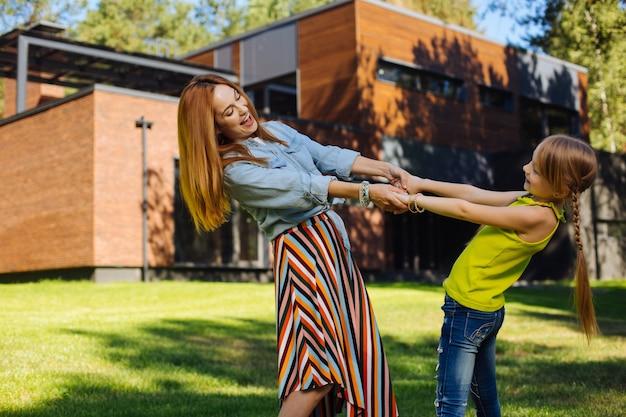 私たちの余暇。笑顔で娘と楽しんでいるインスピレーションを得た金髪の母親