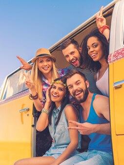 私たちの生活は充実していて幸せです。カメラに微笑んで、レトロなミニバンの中に座って身振りで示す幸せな若者のグループ