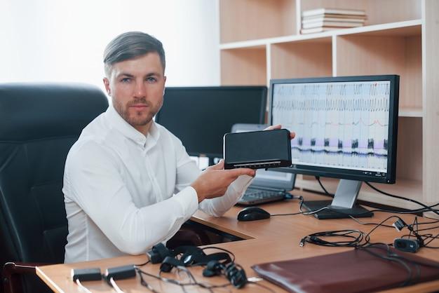 우리의 새로운 장치. 거짓말 탐지기 검사관은 거짓말 탐지기 장비를 가지고 사무실에서 일합니다.