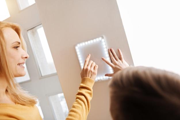 私たちの新しい家。息子にそれを使用するように教えている間、笑顔でスマートホームのコントロールパネルを指さしている楽しい素敵な喜んでいる女性