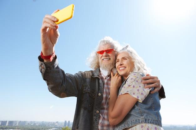 Наше фото. веселый позитивный мужчина держит смартфон, фотографируя его и его жену