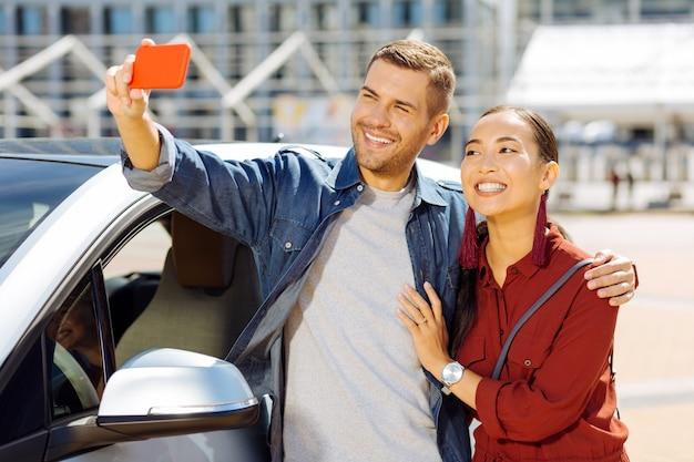 私たちの写真。彼のガールフレンドと一緒に立っている間selfieを取る幸せな素敵な男