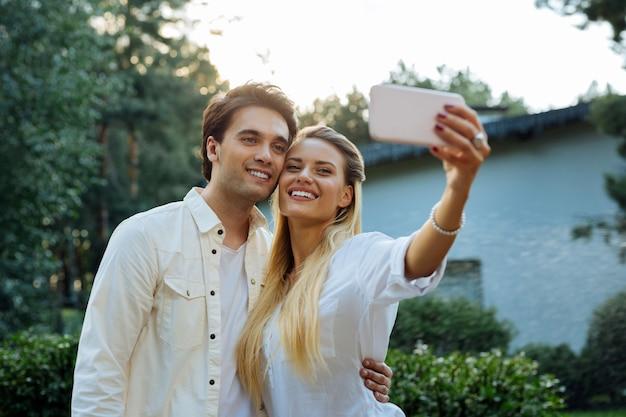 私たちの写真。彼らの自分撮りをしながら一緒に立っているうれしそうな素敵なカップル