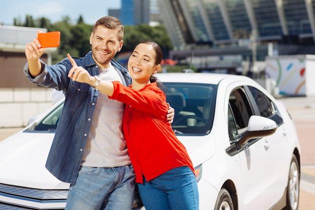 私たちの写真。彼氏と車の近くで写真を撮っている間、スマートフォンの画面を指して素敵な幸せな女性