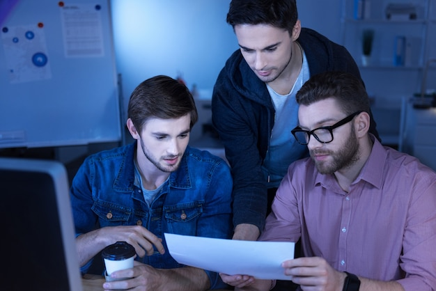 Our project. nice good looking male programmers looking at their notes and developing a plan while working together on the project
