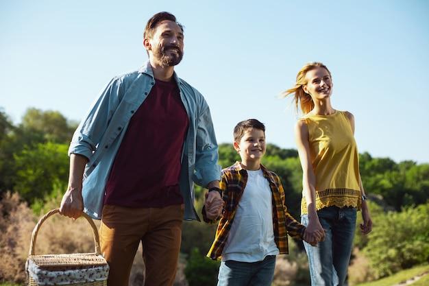 우리의 레크리에이션. 바구니를 들고 아내와 아들과 함께 걷는 콘텐츠 수염 난 아버지