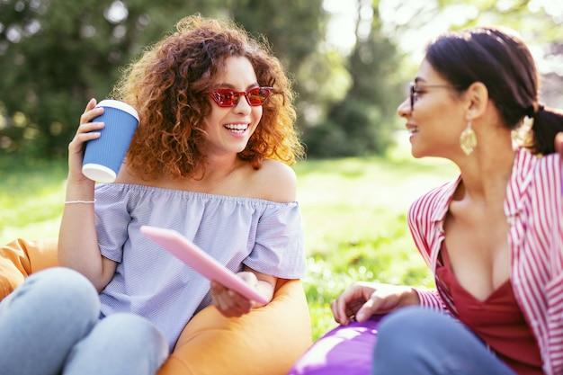 私たちのレクリエーション。タブレットを持って友達と話しているかなりインスピレーションを得た女性