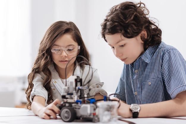 私たちの科学実験。実験室に座って集中力を表現しながらロボットを作成する才能のある有能な子供たち