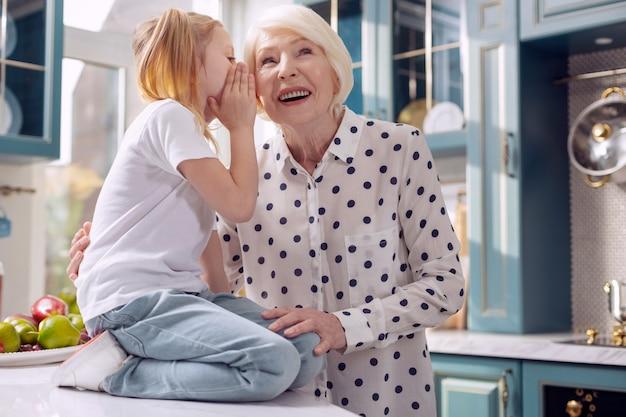 Наш секрет. очаровательная маленькая девочка сидит на кухонном столе и шепчет на ухо своей бабушке, в то время как женщина внимательно слушает и улыбается