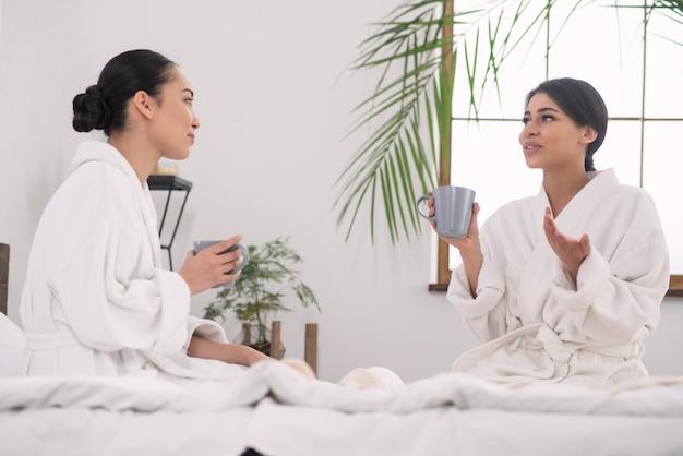 私たちの秘密。ビューティーサロンでお茶を楽しみながらおしゃべりする気持ちのいい姉妹たち