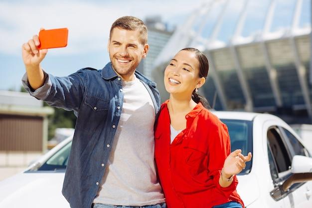 私たちの自撮り。スマートフォンで写真を撮りながら笑顔で幸せな幸せなカップル