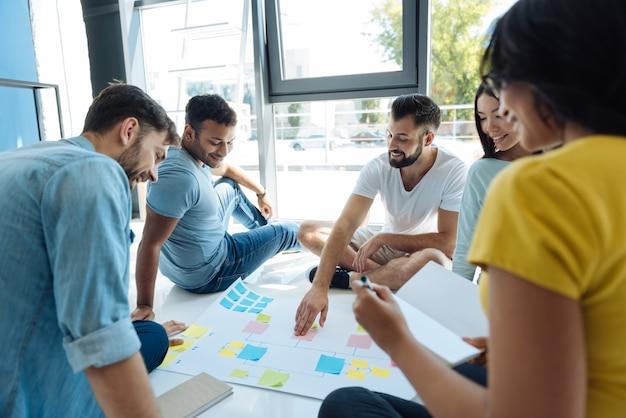우리의 전략. 긍정적 인 창조적 인 사람들은 서클에 앉아 팀에서 일하면서 프로젝트를 논의했습니다.