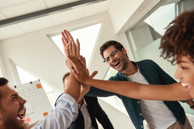 우리의 성공 비즈니스 사람들은 서로 하이파이브를 주고 함께 일하면서 웃고 있습니다.