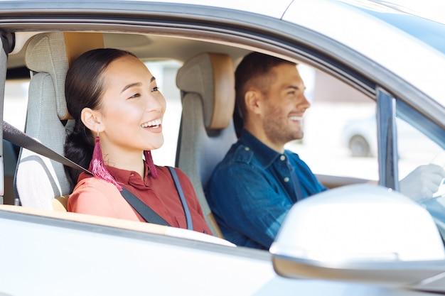 私たちの旅。一緒に旅行をしながら車に座っているポジティブな素敵なカップル