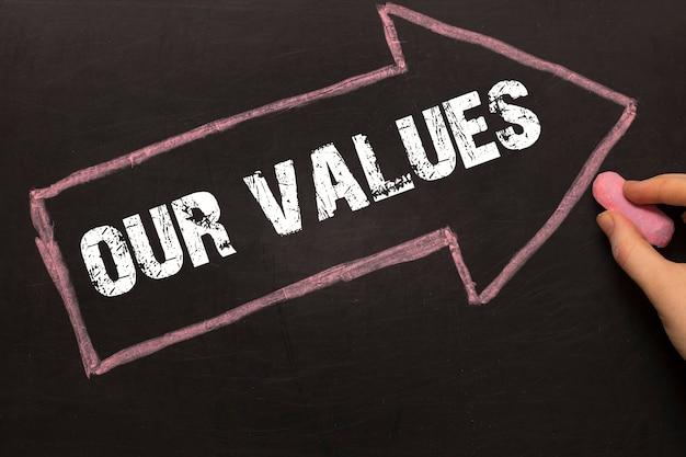 Наши ценности - классная доска со стрелкой на черном фоне