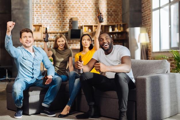 Наша победа. четыре привлекательных энергичных веселых друга пьют пиво, сидя на диване и празднуют гол во время игры