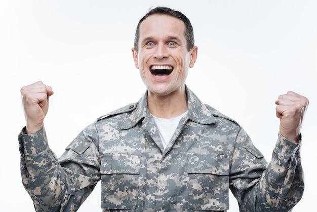 Наша победа. радостный хороший военный мужчина улыбается и поднимает руки, выражая свои эмоции по поводу победы
