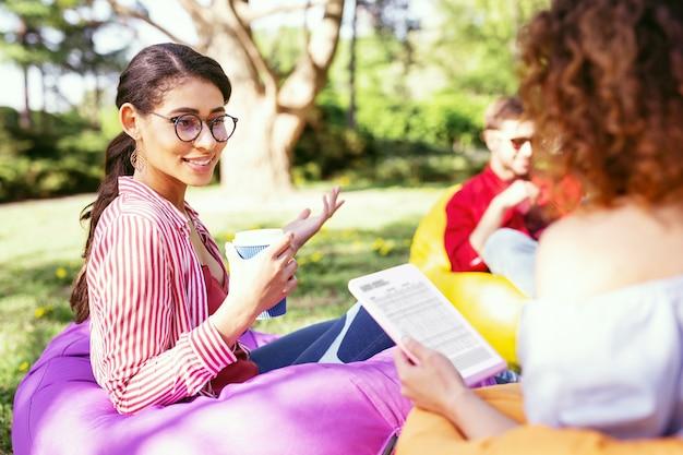 私たちの営業日。野外に座ってプロジェクトに取り組んでいる幸せな野心的な同僚